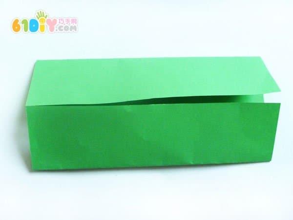 端午节是我国的一个传统节日,它有着独特的风俗,吃粽子、赛龙舟、挂香袋……我们就来做一些五彩缤纷的糖果粽子吧。  手工材料:彩色纸、胶水、剪刀、订书机、贴纸  制作步骤:   1-2、长方形纸(10*15厘米),往中心位置折叠。  3、用胶水粘贴好。  4、用订书机把其中一头订好,形成一个小袋子。没有订书机,也可以直接用胶水来粘贴。  5、装入糖果或饼干,再把袋子的另一头也订好。  6、在粽子的表面贴上漂亮的贴纸,糖果粽子就做好了。如果小朋友们有漂亮颜色的信封也可以用来制作纸粽子