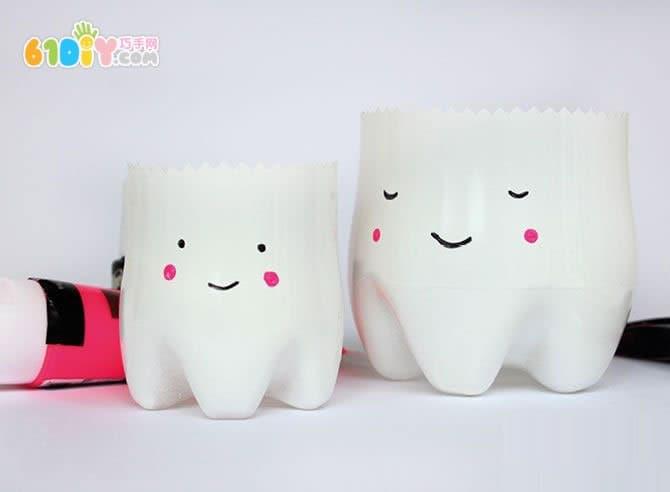 制作可爱的牙齿宝宝牙刷杯  手工材料:可乐瓶、喷漆、剪刀、颜料  配上白漆  剪下底部来  画上眼睛嘴巴  可爱的牙齿宝宝就做好了